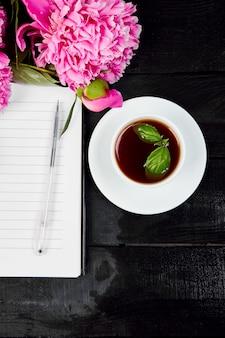 Pfingstrosenblumen auf schwarzem hintergrund mit notiz oder tagebuch a
