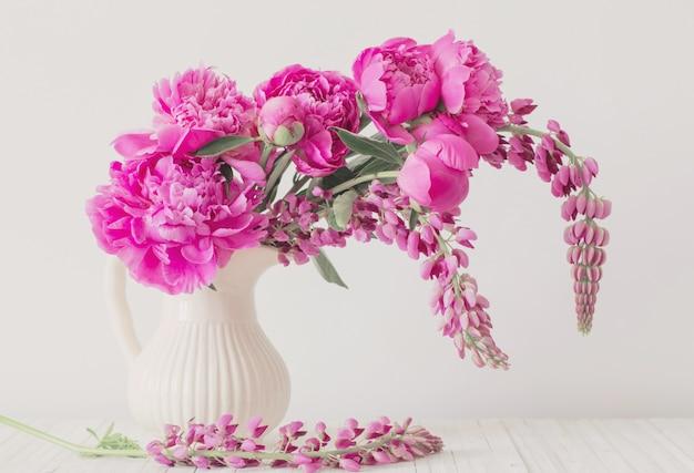 Pfingstrosenblumen in der vase auf weißer wand