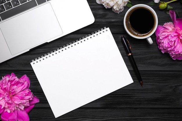 Pfingstrosenblumen, kaffee, stift, laptop und leeres notizbuch für ihren text auf einem schwarzen holz
