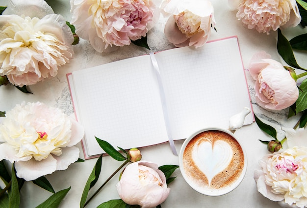 Pfingstrosenblumen, notizbuch und kaffee