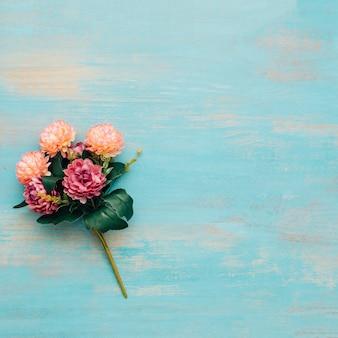 Pfingstrosenblumenstrauß auf blauem hölzernem hintergrund.