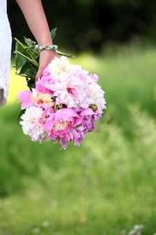 Pfingstrosenblumenstrauß in der hand der frau draußen