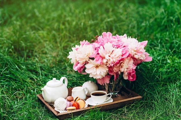 Pfingstrosenblumenvase, teekanne und tasse tee und makronen auf einem holztablett.
