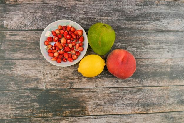 Pfirsich, birne, zitrone auf einem hölzernen hintergrund. holzblöcke mit den worten vitamin c, frisches obst im hintergrund, gesundes essen oder diätkonzept. von oben betrachten. platz zum schreiben.
