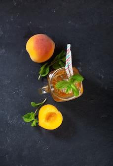 Pfirsich-eistee auf dunklem hintergrund mit minze und eis, schönes getränk für die heiße sommerzeit