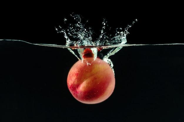 Pfirsich fiel mit blasen ins wasser