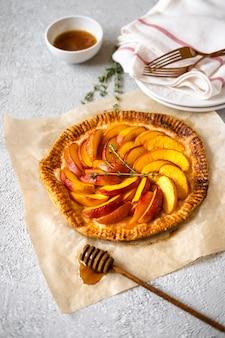 Pfirsich galette, kuchen, kuchen mit honig auf grau