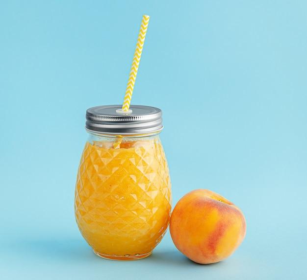 Pfirsich-smoothie-glas mit gelbem trinkhalm auf blauer wand.
