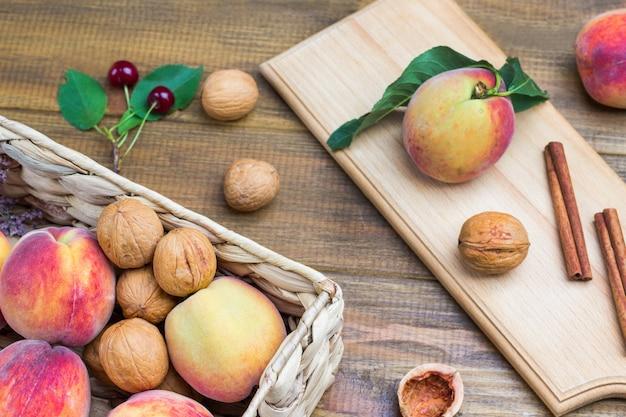 Pfirsiche im weidenkorb. walnüsse und zimtstangen auf holzbrett. hölzerner hintergrund. flach legen