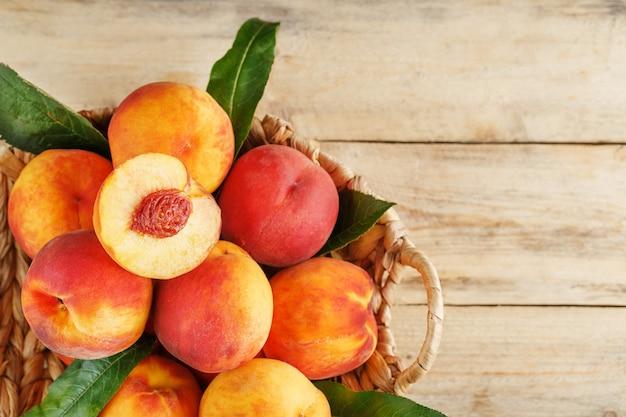 Pfirsiche in einem korb auf einem hölzernen hintergrund mit einer scheibe geschnittenen saftigen pfirsichs mit einem stein. rustikaler stil
