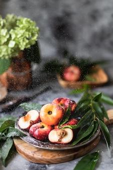 Pfirsiche mit frischen früchten mit blättern auf einer teller-nahaufnahme.