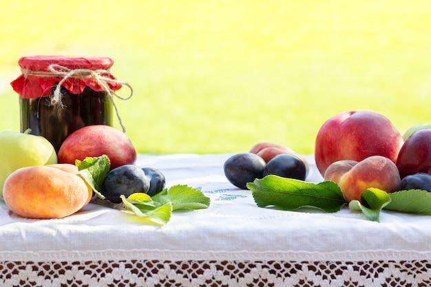 Pfirsiche mit frischen früchten, nektarinen, pflaumen und hausgemachte marmeladengläser