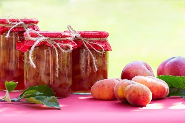Pfirsiche mit frischen früchten, nektarinen und hausgemachte marmeladengläser