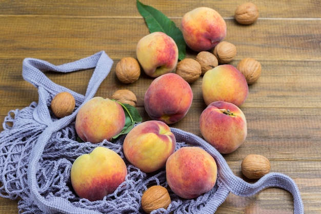 Pfirsiche mit grünen blättern im stoffbeutel. hölzerner hintergrund. ansicht von oben