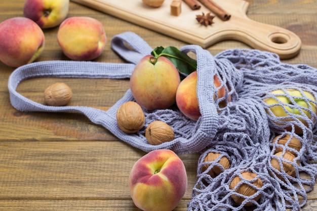 Pfirsiche mit grünen blättern im stoffbeutel. walnüsse, zimtstangen und sternanis an bord. hölzerner hintergrund. ansicht von oben