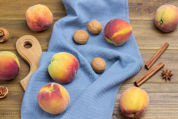 Pfirsiche und walnüsse auf grauer serviette. zimtstangen und sternanis auf dem tisch. hölzerner hintergrund. ansicht von oben