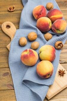 Pfirsiche und walnüsse auf holzbrett auf grauer serviette. hölzerner hintergrund. ansicht von oben