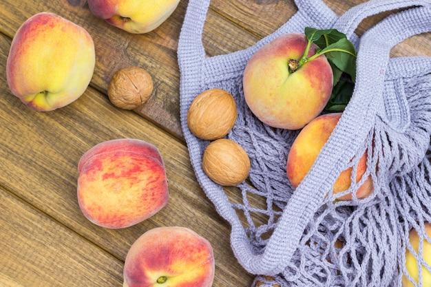 Pfirsiche und walnüsse in grauem stoffnetz. pfirsiche und zimtstangen auf dem tisch. hölzerner hintergrund. flach legen