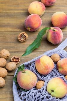 Pfirsiche und walnüsse in grauem stoffnetz. walnüsse auf dem tisch. hölzerner hintergrund. ansicht von oben