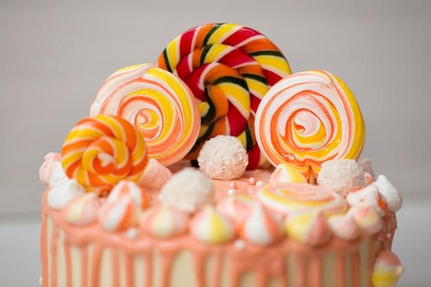 Pfirsichfarbener kuchen mit baiser und süßigkeiten zum geburtstag eines kindes