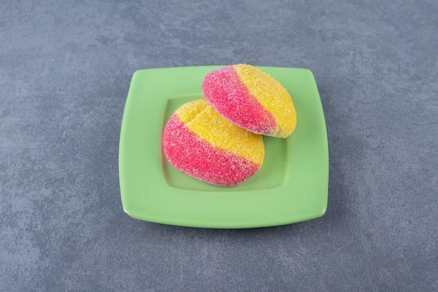 Pfirsichförmiger keks in zwei hälften auf einem teller auf marmortisch teilen.
