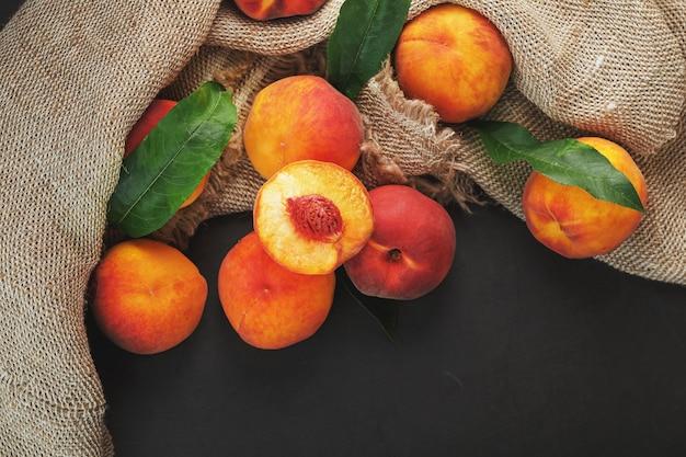 Pfirsichfrucht auf einem schwarzen hintergrund mit einem tuch aus sackleinen und grünen blättern. süße und saftige pfirsichscheiben mit einem stein