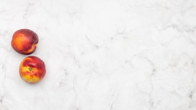 Pfirsichfrucht auf marmorhintergrund