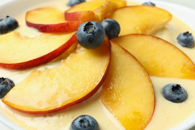 Pfirsichjoghurt mit heidelbeer- und pfirsichscheiben, nahaufnahme