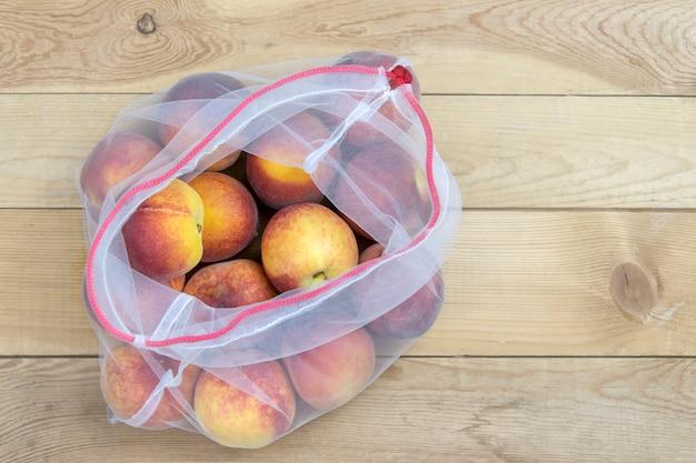 Pfirsichnahaufnahme in einer einkaufstüte auf einem hölzernen hintergrund