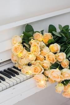 Pfirsichrosen mit girlanden auf einem weißen klavier