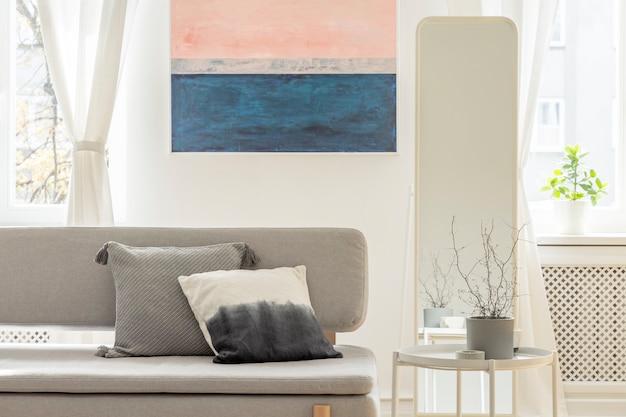 Pflanze in grauem topf auf weißem couchtisch neben stilvoller grauer couch mit kissen