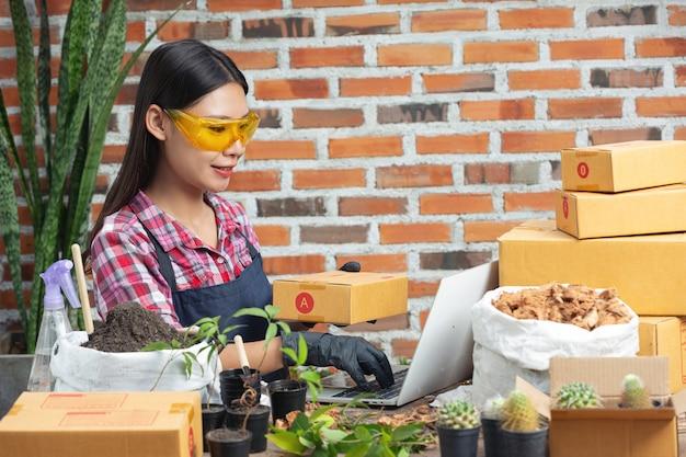 Pflanze online verkaufen; frauen lächeln, während sie laptop benutzen