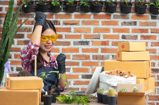 Pflanze online verkaufen; frauen sind froh, wenn sie einen laptop benutzen
