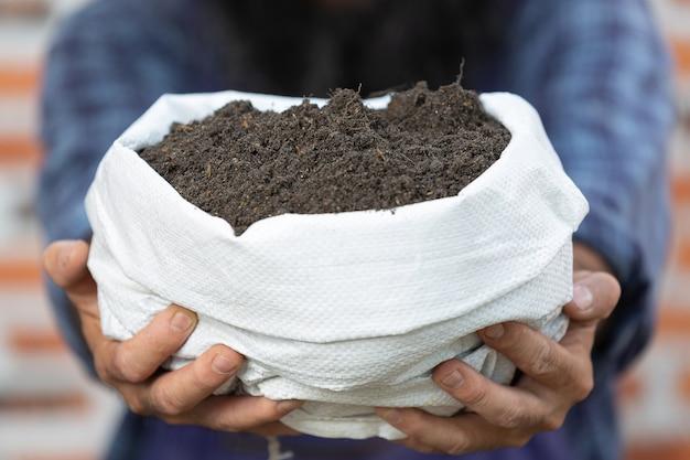 Pflanze online verkaufen, nahaufnahmebild der hand, die sack erde hält
