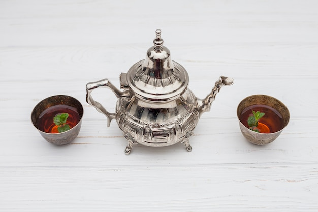 Pflanzen in tassen tee in der nähe von vintage teekanne