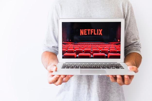 Pflanzen sie den kerl, der laptop mit netflix-logo hält