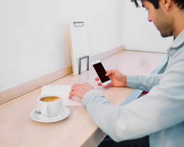 Pflanzen sie den mann, der mit papieren und smartphone arbeitet
