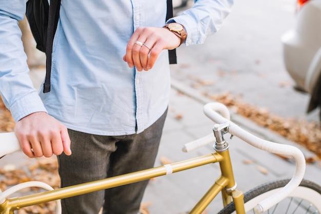 Pflanzen sie den mann, der uhr nahe fahrrad betrachtet