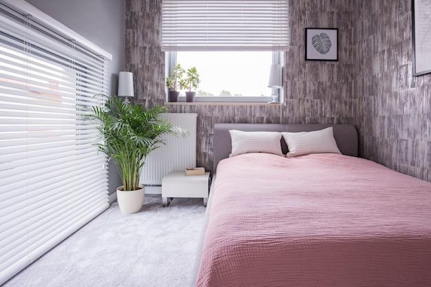 Pflanzen sie neben dem bett mit rosa laken und kissen im hellen schlafzimmer mit fenstern. echtes foto