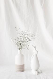 Pflanzen sie zweige mit blumen in der vase und figur des kaninchens