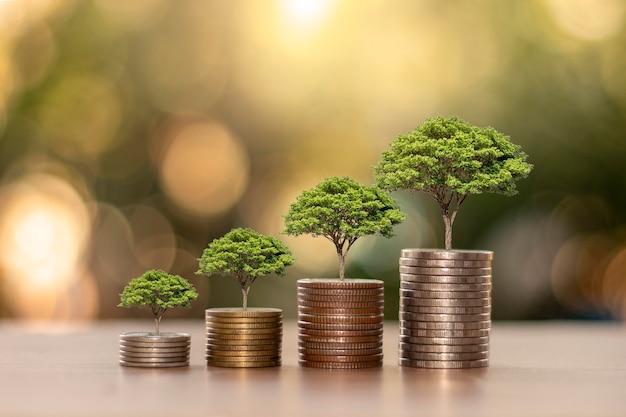 Pflanzen wachsen auf haufen von münzen oder geld auf den holzböden, das konzept des geldsparens, des wirtschaftswachstums und der finanzierung einer nachhaltigen entwicklung.