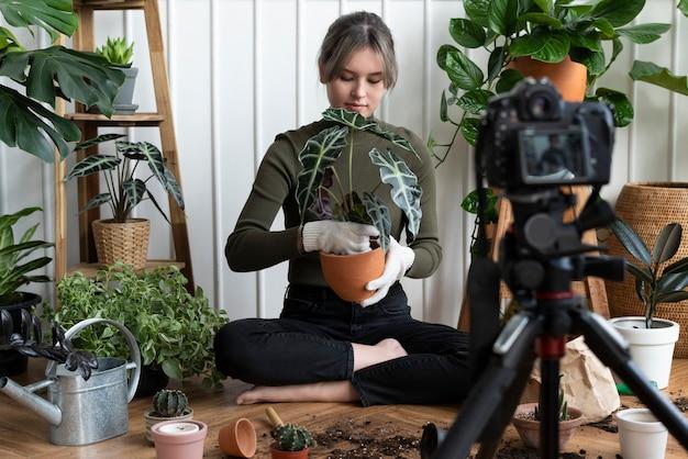Pflanzenbloggerin filmt ein video von sich selbst beim pflanzen