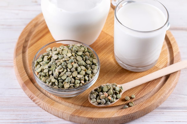 Pflanzenmilch auf basis grüner erbsen auf einem weißen holztisch. glutenfreies, sojafreies, laktosefreies produkt