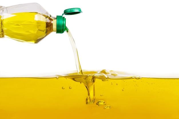 Pflanzenöl, das auf pflanzenölhintergrund gießt