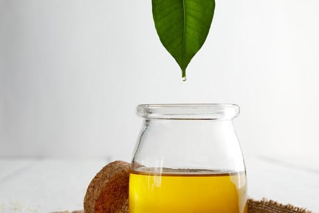 Pflanzenöl, das von einem grünen blatt in eine glasflasche fällt. nahaufnahme