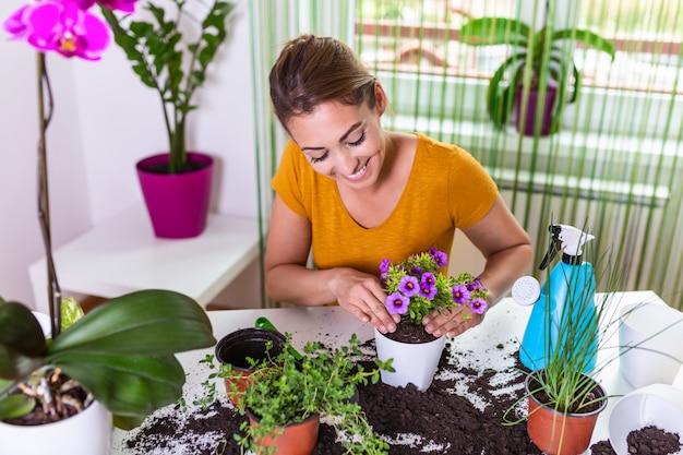 Pflanzenpflege. gartenarbeit ist mehr als hobby. schöne hausfrau mit blume im topf und gartenset. pflege für eine topfpflanze