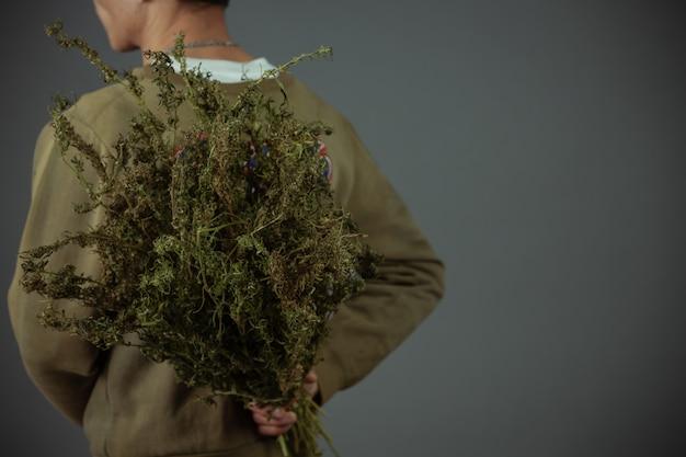 Pflanzer halten cannabisbäume auf einem grauen hintergrund.