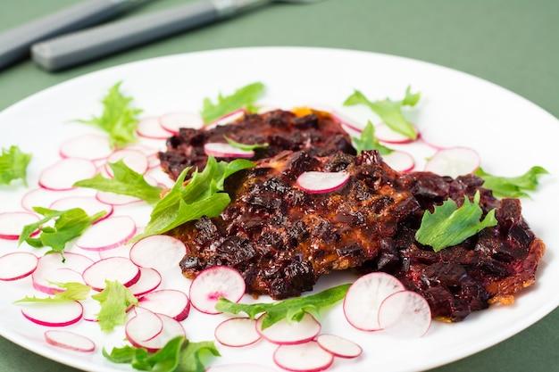 Pflanzliche diätkost. rote-bete-steak, rettich und friessalatblätter auf einem teller auf einem grünen tisch. nahansicht