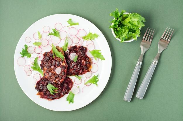 Pflanzliche diätkost. rote-bete-steak, rettich und friessalatblätter auf einem teller und gabeln auf einem grünen tisch