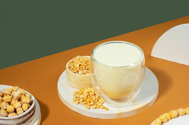 Pflanzliche erbsenmilch in einer flasche und kichererbsen in einer schüssel auf weißem podest, sockel auf beigegrünem hintergrund. schatten.gluten- und laktosefreies veganes produkt.moderne zusammensetzung.isometrische diagonalprojektion